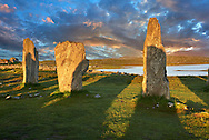 Outer row of stones, 27 metres long at sunset,  leading to the central stone circle overlooking Loch Roag, circa 2900BC. Calanais Neolithic Standing Stone (Tursachan Chalanais) , Isle of Lewis, Outer Hebrides, Scotland. .<br /> <br /> Visit our SCOTLAND HISTORIC PLACXES PHOTO COLLECTIONS for more photos to download or buy as wall art prints https://funkystock.photoshelter.com/gallery-collection/Images-of-Scotland-Scotish-Historic-Places-Pictures-Photos/C0000eJg00xiv_iQ<br /> '<br /> Visit our PREHISTORIC PLACES PHOTO COLLECTIONS for more  photos to download or buy as prints https://funkystock.photoshelter.com/gallery-collection/Prehistoric-Neolithic-Sites-Art-Artefacts-Pictures-Photos/C0000tfxw63zrUT4