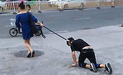 Shocking moment a woman takes her male companion for a walk on a DOG LEASH in China <br /> <br /> Bizarre images have emerged of a woman taking a man for a walk on a dog leash across a road in China. The pair were spotted on September 9 in Fuzhou, China's Fujian province. Police had to be called to deal with the issue as the pair were holding up traffic and causing traffic jams. <br /> <br /> According to reports, the woman was spotted walking with the man on a leash. He was crawling on the floor like a dog. The woman was then spotted patting the man on his head. The pair caused traffic jams in the city and police had to be called in. They managed to persuade her to untie the rope and free the man. <br /> ©Exclusivepix Media