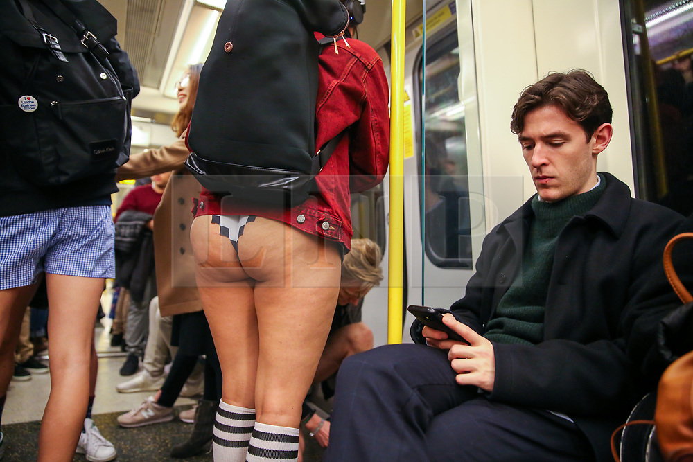 """© Licensed to London News Pictures. 13/01/2019. London, UK. Participants take part in 10th anniversary of 'No Trousers Tube Ride' event by travelling on the District Line on the London underground to surprise fellow passengers. The """"No Pants Subway Ride"""" is an annual event staged by Improve Everywhere every January in New York City. The mission started as a small prank with seven guys and has grown into an international celebration of silliness, with dozens of cities including London around the world participating each year. Photo credit: Dinendra Haria/LNP"""