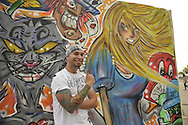 Garden City, New York, USA. September 14, 2014. JEAN PAUL SALIBA, aka Draft, of Farmingdale, is a graffiti artist creating an outdoor mural of Alice in Wonderland characters, at the United Ink Flight 914 tattoo convention at the Cradle of Aviation museum of Long Island.
