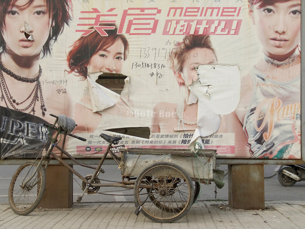 a dilapidated advertising billboard with an bicycle cart parked in front of it Beijing China