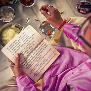 A Pandit (priest), who has selected the day of the wedding based on the bride and groom's horoscopes, reads holy Sanskrit mantras during a Hindu wedding.<br /> Delhi, 2010