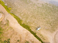 Aerial view of a boat moored in wetlands of Formosa lagoon in Portugal.