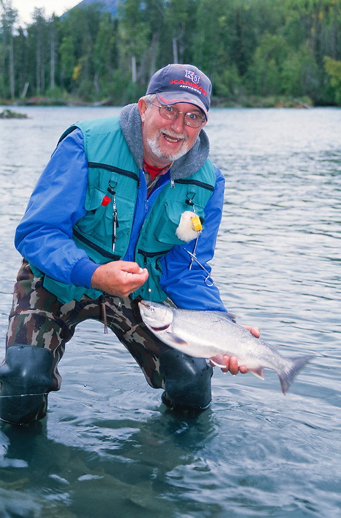 Alaska. Kenai Peninsula. Kenai River. Fly fisher with large dolly varden. PLEASE CONTACT US FOR DIGITAL DOWNLOAD AND PRICING.