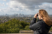 A woman looking through binoculars at the City of London from Severndroog Castle on the 6th October 2019 in London in the United Kingdom. Severndroog Castle is a folly situated in Oxleas Wood, on Shooters Hill in south-east London in the Royal Borough of Greenwich. It was designed by architect Richard Jupp, with the first stone laid on 2 April 1784.