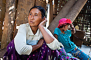 A grandmother and granddaughter take shelter from the afternoon sun during a day of rice planting.