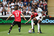 Tammy Abraham of Swansea city shields the ball from Phil Jones of Manchester Utd. Premier league match, Swansea city v Manchester Utd at the Liberty Stadium in Swansea, South Wales on Saturday 19th August 2017.<br /> pic by  Andrew Orchard, Andrew Orchard sports photography.