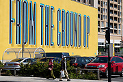 Two residents of Canning Toan, Newham walk past the large lettering that says 'From the Ground Up' on the new Silvertown Way regeneration development in Canning Town, on 11th August 2021, in London, England.