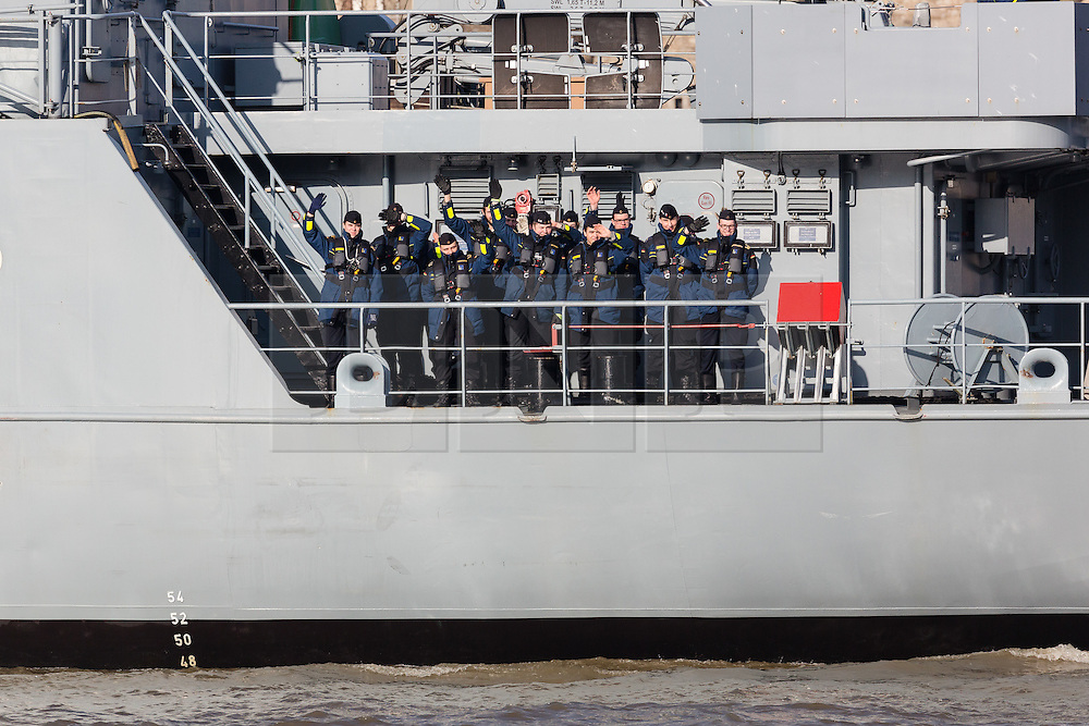 © Licensed to London News Pictures. 13/02/2017. LONDON, UK.  Naval Officers on board wave as the German Navy spy ship, FGS Oker A53 leaves London, passing under Tower Bridge on the River Thames following a short London visit. FGS Oker A53 is one of the Oste class ships, that are purpose built intelligence collection spy ships and were primarily designed to gather data on Soviet warships.  Photo credit: Vickie Flores/LNP.