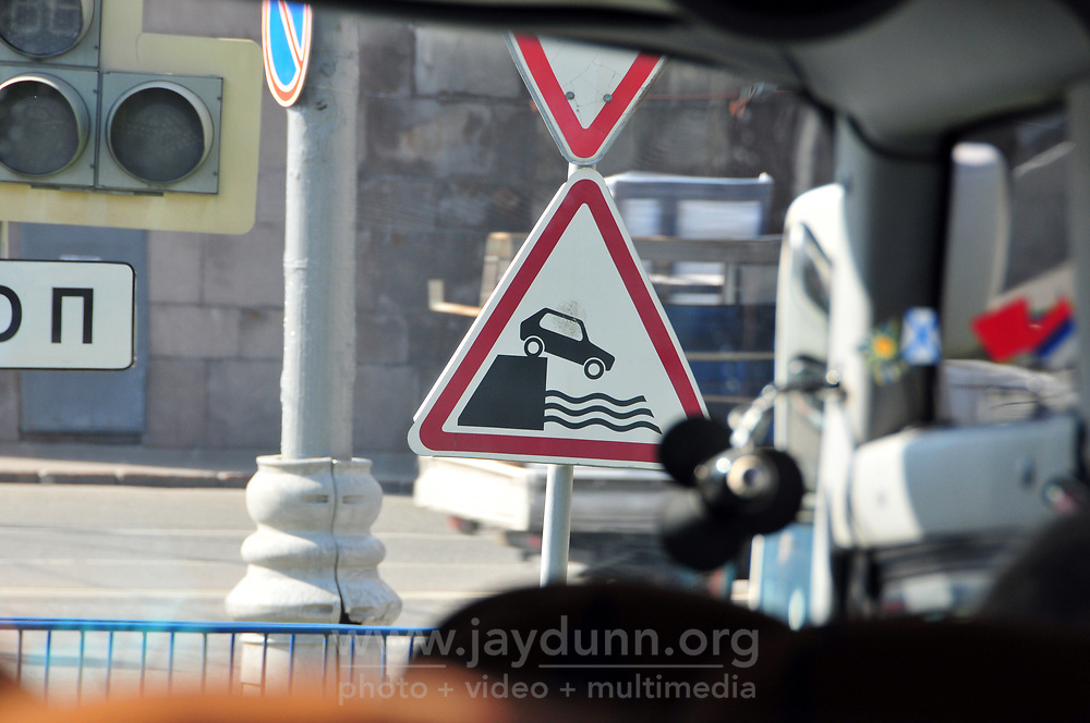 As seen from inside a bus, a road sign indicates danger at a nearby canal. A cosmopolitan city with a nearly 900 year history, Moscow is Russia's financial and administrative capital and home to many of the country's most recognizable architectural gems. Spread over 2500 square kilometers, the city is served by four airports, three ring roads and a world-famous metro. With a population of 13 million, Moscow is the second-most populated city in Europe after Istanbul.
