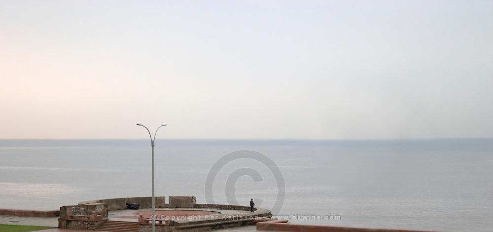 A view over the Rio de la Plata in Montevideo on a rainy day. A man alone standing on a viewing platform overlooking the water and the horizon line Rambla sur and Rambla Gran Bretagna along the River Rio de la Plata Montevideo, Uruguay, South America