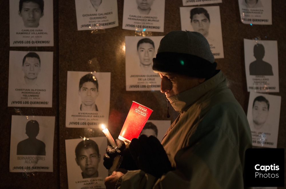 A man holds candles in front of photos of some of the missing students. November 20, 2014.