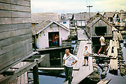 Tourist visiting area of Informal housing wooden shacks built on timber logs known as the Floating City, Manaus, Brazil 1962 removed as part of slum clearance policy in late 1960s