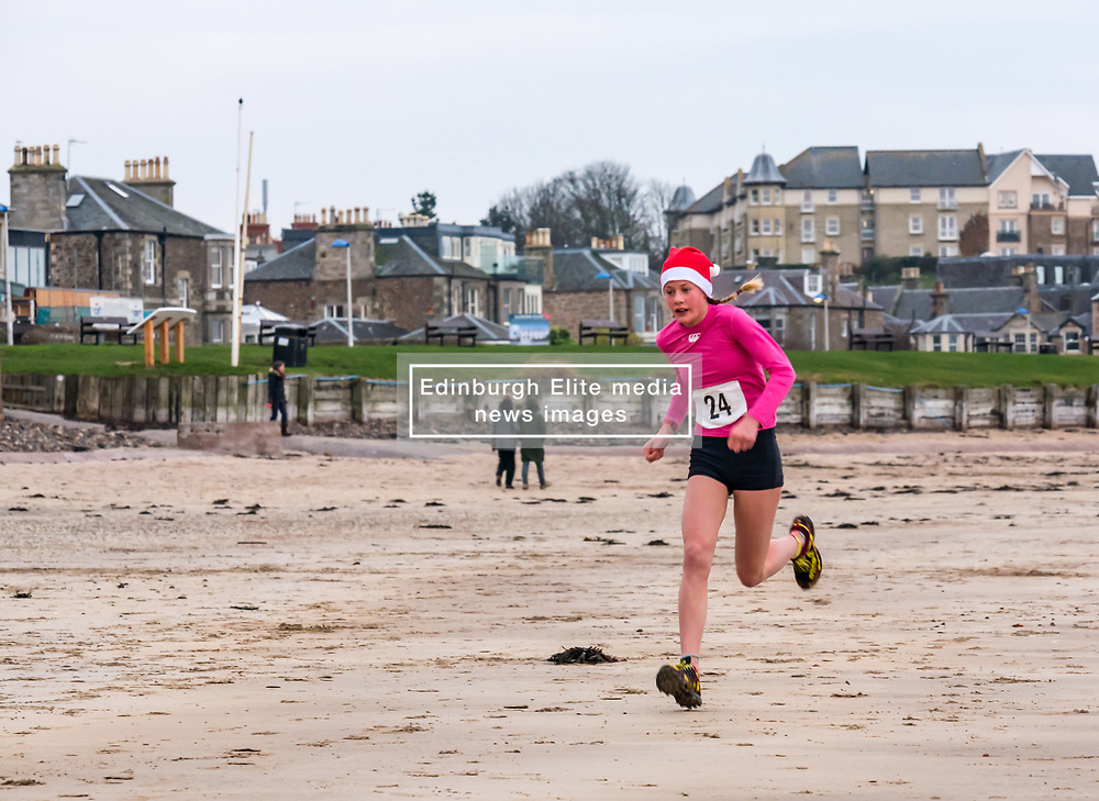 Pictured: Santa Beach Run on the scenic East Lothian coast. This new event is aimed at athletes, casual runners and families. It is hosted by Project Trust with proceeds enabling local school leavers to spend a year volunteering in India/Honduras to teach at a school with few teaching materials. The fastest child who wins the race. 15 December 2018  <br /> <br /> Sally Anderson | EdinburghElitemedia.co.uk