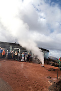 Tourists watch steam rise from geyser spout, Parque Nacional de Timanfaya, national park, Lanzarote, Canary Islands,