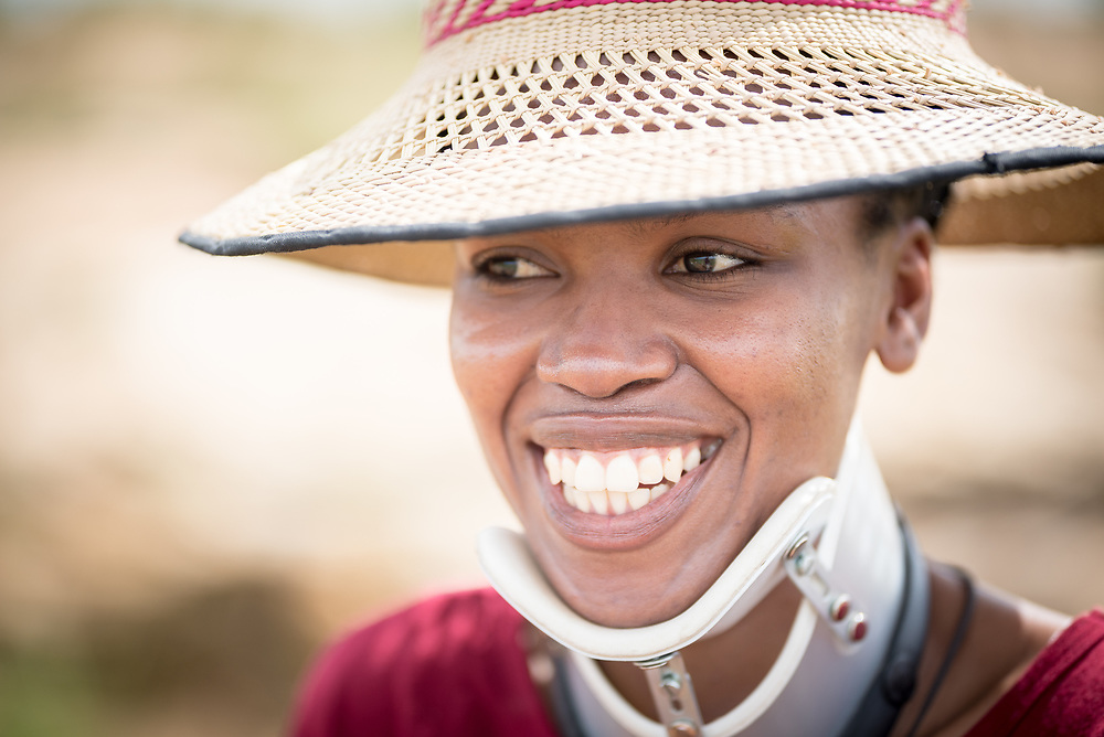 3 March 2017, Thaba Bosiu, Lesotho: Ntaoleng Tlali from the village of Thaba Bosiu visits the mountain of Thaba Bosiu ('Night Mountain') shortly after being in a car accident, after which she is wearing neck support as a precaution against further complications. She is wearing a tsetse, a traditional hat commonly used in Lesotho. Thaba Bosiu is a sandstone plateau some 24 kilometers east of Lesotho's capital, Maseru. The name means Night Mountain, and surrounding the plateau is a small village and open plains. Thaba Bosiu was once the capital of Lesotho, and the mountain was the stronghold of the Basotho king when the kingdom of Lesotho was formed.