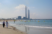 Israel, Hadera, relaxing on the seaside. The Natural Gas and coal operated power plant's flues in the background