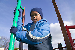 Little boy playing on a climbing frame in the playground,