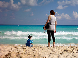 09 Feb 2014. Cancun, Mexico.<br /> Grandmother and grandson on the beach at Isla Cancun along the Zona Hotelera on the Carribean Sea. <br /> Photo; Charlie Varley/varleypix.com