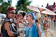 A group of women in wigs and costumes chat and interact with each other in the sun. Glastonbury festival 2010