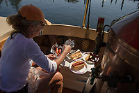 """Perfect timing for a lunch of kielbasa cooked in the wood fired copper plated firebox of the """"Phoenix"""" with Kristie LeGates as chef and first mate after making the trek from Lees Mill, Moultonboro to 19 Mile Bay, Tuftonboro on Wednesday.  (Karen Bobotas/for the Laconia Daily Sun)"""