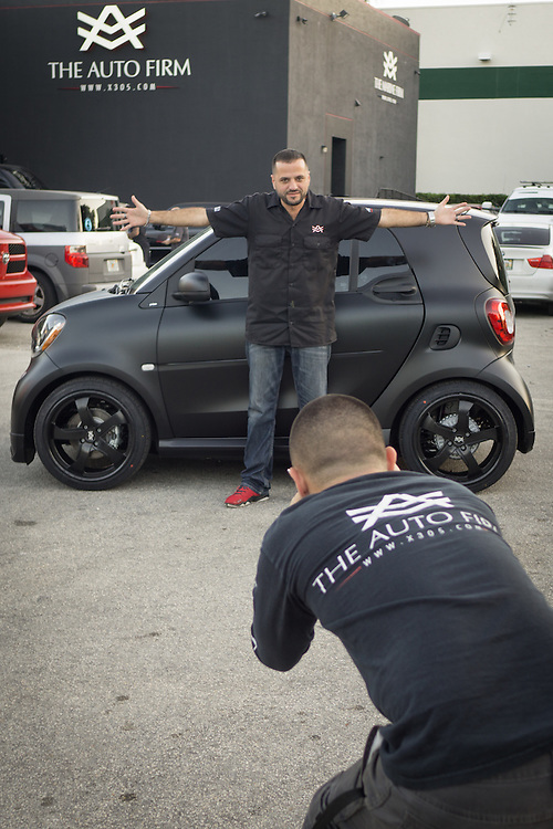 DORAL, FLORIDA, DECEMBER 11, 2015<br /> Alex Vega, owner of The Auto Firm, a South Florida car customizing and restoring shop which has a vast clientele of professional athletes and entertainers, poses as his son Alex Vega Jr. takes photos of a customized Smart Car. The vehicle was done for former NFL player Chad Johnson, also known as Ochocinco.<br /> (Photo by Angel Valentin/Freelance)