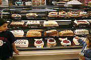 (MODEL RELEASED IMAGE). The Fernandezes begin their Sunday grocery trip after lunch. Clutching their spending money, Brianna and Brian head for the bakery case in their local San Antonio, Texas supermarket, where they settle on giant pan dulces. Hungry Planet: What the World Eats (p. 272).