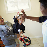 Supportive Housing program case worker, Melissa (in white shirt) spends time with client Irma and Irma's son, Julio, age 18 months. Irma's house was provided with the assistance of the Supportive Housing program in Connecticut. Melissa has provided support to Irma for over two years. <br /> <br /> Irma, age 24, left home at the age of nine after she and her brother suffered abuse at the hands of their step father. After several years in the care of foster homes and living homeless, Irma became pregnant at age 15. By the age of 23, Irma had lived through periods of homelessness and had become mother to four children with two different men, both of whom were abusive. Six months into her fourth pregnancy, Irma's partner threw her down the stairs and she went into premature labour. Medical staff told Irma that she would miscarry but her youngest son, Julio survived after spending the first six months of his life in hospital. The sustained involvement of medical professionals in Irma's life alerted the Supportive Housing program to her situation. Case worker Melissa began working with Irma, offering support, advice and providing the funds to purchase items for the care of baby Julio. Melissa made representations to the Department of Children and Families (DCF) to vouch for Irma's character and convince them that Irma should not be separated from her children. Melissa encouraged Irma to go back to school and complete her high school diploma. <br /> <br /> Supportive Housing  provided Irma a housing-voucher so that she could keep her children and live independently of her abusive partner. Irma now lives with her children who have rooms of their own and a back yard in which to play. Julio, now eighteen months, has significant health needs but the relative stability of Irma's life now means she can look to the future with a sense of optimism. She hopes to complete her associates degree in nursing and eventually earn an income that will allow her to live in accommod