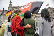 """Protesters comfort an Afghan refugee as people take part in a demonstration in front the Reichstag  building, seat of the German lower house of Parliament, the Bundestag in Berlin, Germany, August 17, 2021. About 1000 people gathered in front of the  under the call """"Airlift now! Create safe escape routes from Afghanistan!"""", the spontaneous event was organized by Seebrücke and several other human-rights organizations."""