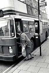 Elderly woman getting on a bus, Nottingham UK 1989
