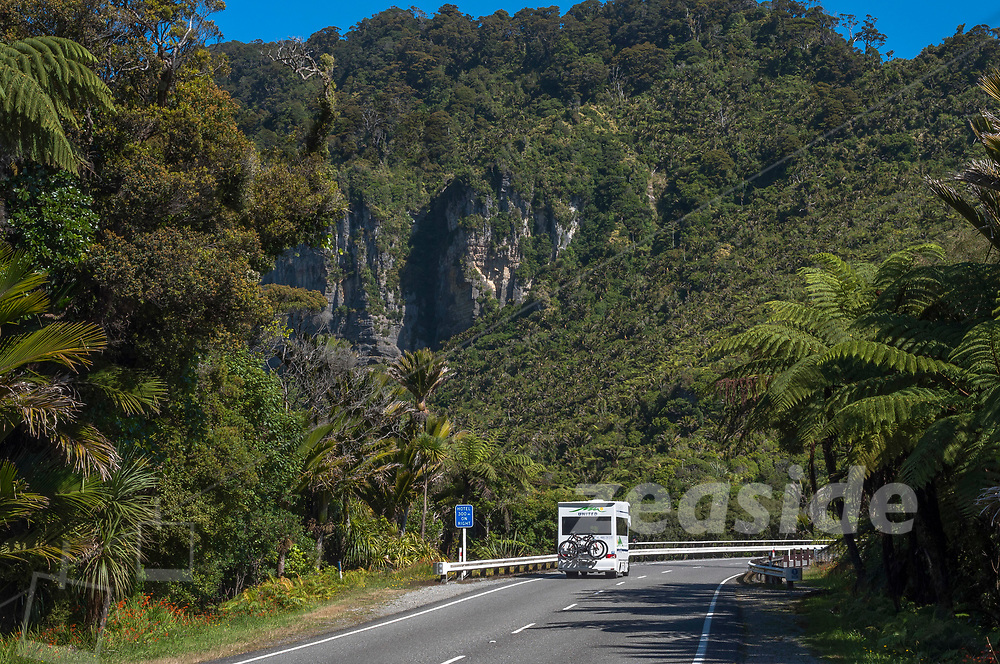 """A motor camper wanders along State Highway 6, crossing the Pororari River gorge near Punakaiki. A sign amidst the rainforest reads: """"Hotel 300m on right""""."""