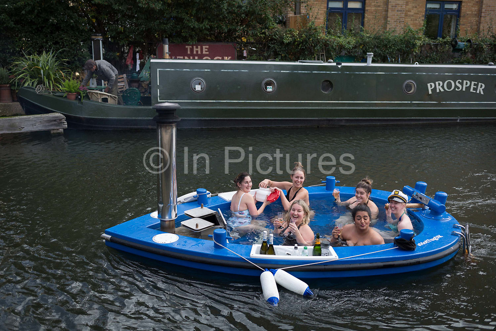 Women float along the cold waters of the Regents Canal in a hot tub from the company HotTug, on 22nd October, in London, England. The HotTug is a design by Frank de Bruijn, who works on a barge in the port of Rotterdam. Its constructed from wood and fitted with glass-fibre reinforced polyester and is powered by a built-in electric motor so is very quiet.