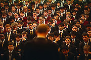 Looking down from a high vantage point, we see boy pupils seated as they gather in front of the Headmaster during morning assembly at the City of London School for boys in central London. Individual faces in neat rows stretch into the distance as we look past the Headmaster who is addressing, facing his students. Some seem serious, a few are looking bored while one boy can be seen coughing into his hand and another looking away with a smirk.  We can see a diverse range of ethnic backgrounds, skin colours and hairstyles. The City of London School (CLS) is a boys' public school on the banks of the River Thames. It traces its origins to a bequest of land by John Carpenter, town clerk of London in 1442. The City of London has a resident population of under 10,000 but a daily working population of 311,000. The City of London is a geographically-small City within Greater London, England. The City as it is known, is the historic core of London from which, along with Westminster, the modern conurbation grew. The City's boundaries have remained constant since the Middle Ages but  it is now only a tiny part of Greater London. The City of London is a major financial centre, often referred to as just the City or as the Square Mile, as it is approximately one square mile (2.6 km) in area. London Bridge's history stretches back to the first crossing over Roman Londinium, close to this site and subsequent wooden and stone bridges have helped modern London become a financial success.