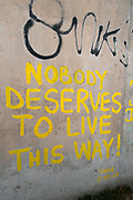 France , Calais, camp for refugees known as 'The Jungle'. September 21st 2015. The words 'Nobody deserves to live this way' are painted on the side of the flyover wall.