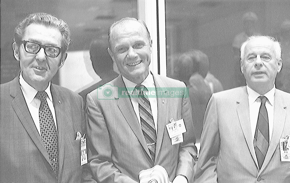 On hand in Houston's mission control center to witness activity associated with the landing and recovery operations for the Apollo 11 mission on July 24,1969 were, from the left, Bob Kline, chief of the Mission Operations Procurement Branch at the Manned Spacecraft Center (MSC); astronaut John H. Glenn Jr.; and Eberhard Rees, deputy director of the Marshall Space Flight Center (MSFC). They were among a large number of personnel on hand in the MCC's mission operations control room (MOCR). Glenn holds one of the dozens of flags that were handed out for the return's celebration. Photo by NASA via CNP/ABACAPRESS.COM