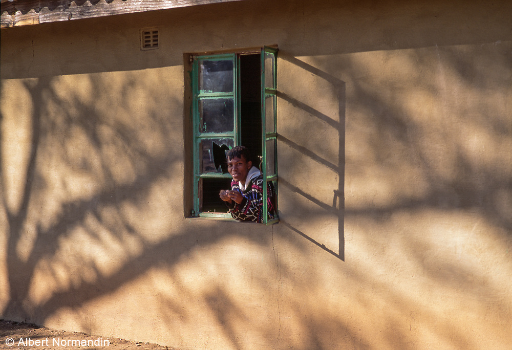 Teacher in window with shadow, Detema School, Zimbabwe, May 1995