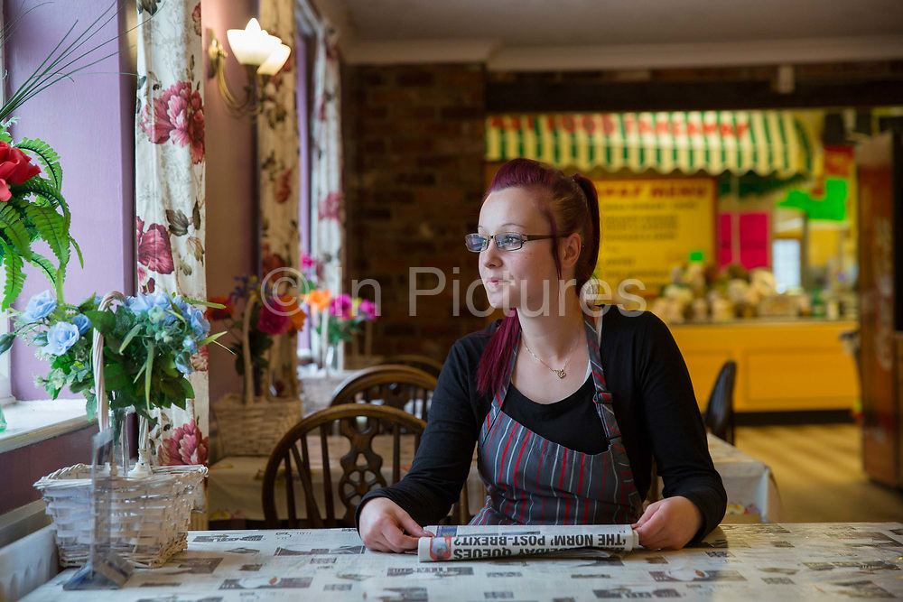 A waitress takes a break a the Farm Cafe in rural Holbeach on the 23rd June 2017 in Norfolk, United Kingdom. Established during the 1950's after the owners parents set up a tea stop on the east bound A17, the cafe has grown over the years and attracts coach loads of tourist and travellers often en route to the north Norfolk coast.