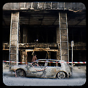 A burned out building on Ermou Street.<br /> <br /> Following the murder of a 15 year old boy, Alexandros Grigoropoulos, by a policeman on 6 December 2008 widespread riots, protests and unrest followed lasting for several weeks and spreading beyond the capital and even overseas<br /> <br /> When I walked in the streets of my town the day after the riots I instantly forgot the image I had about Athens, that of a bustling, peaceful, energetic metropolis and in my mind came the old photographs from WWII, the civil war and the students uprising against the dictatorship. <br /> <br /> Thus I decided not to turn my digital camera straight to the destroyed buildings but to photograph through an old camera that worked as a filter, a barrier between me and the city.