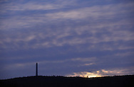 Wantage, New Jersey- The moon, at right, sets behind clouds near the High Point Monument on Dec. 20, 2011. ©Tom Bushey / The Image Works