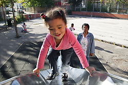 Young girl walking up a slide in a playground with her Grandmother watching,