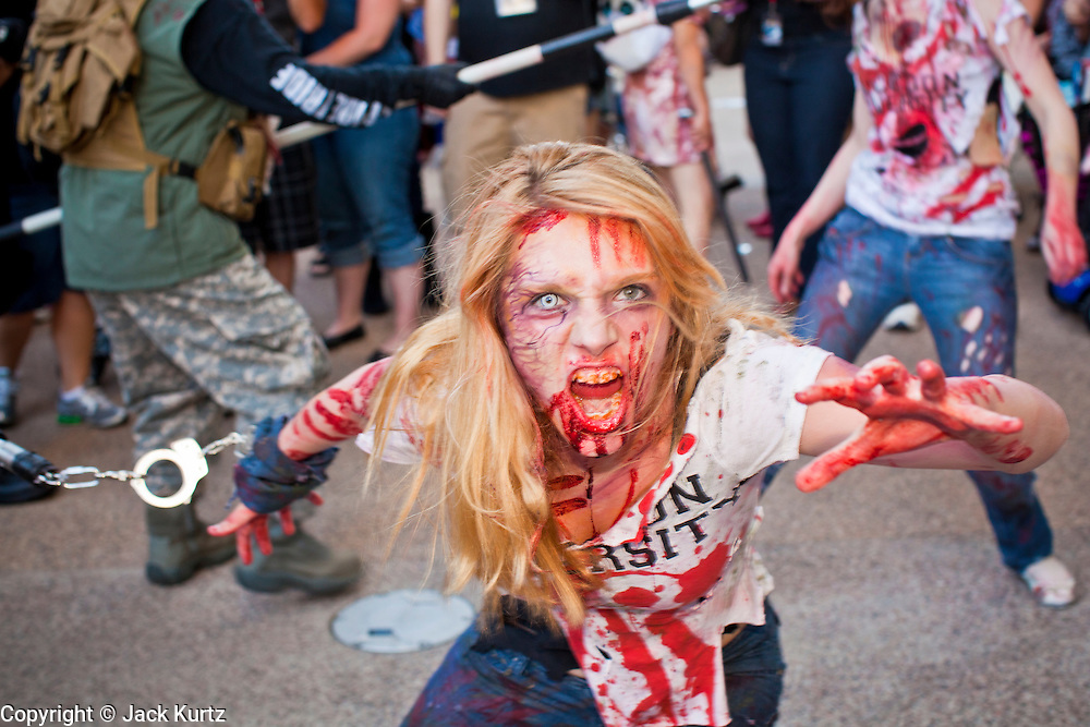 27 MAY 2011 - PHOENIX, AZ: Zombies walk through downtown Phoenix during the Comicon Zombie Walk Friday. Phoenix Comicon opened Thursday and featured a Zombie Walk through downtown Phoenix Friday night. Hundreds of people participated in the Zombie Walk, both as Zombies and as Zombie hunters. This year's Comicon includes appearances by Leonard Nimoy (Star Trek), Adam Baldwin (Firefly and Chuck), Stan Lee (Marvel Comics), Nicholas Brendon (Buffy the Vampire Slayer) and others. Activities include costuming workshops, role playing games and a Geek Prom.     Photo by Jack Kurtz