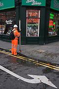Surveyor dressed in orange high-vis suit stands outside Soho sex bookshop.