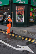 Surveyor dressed in orange high-vis suit stands outside Soho sex bookshop.