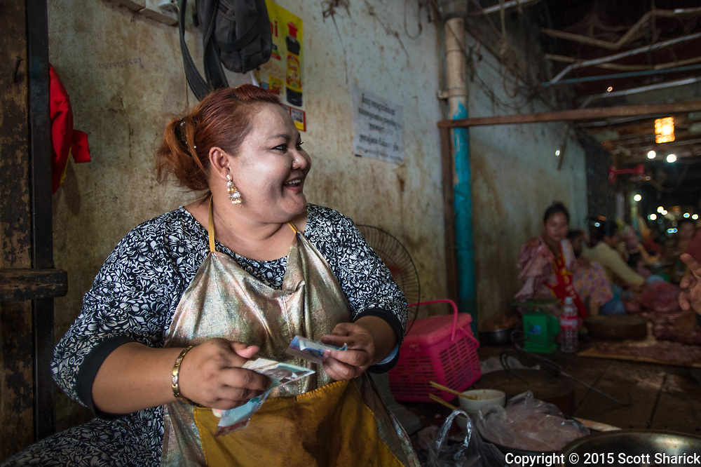 A Cambodian woman gets change ready at the Phsa Leu market in Siem Reap Cambodia