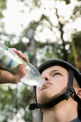 Teenage boy drinking water from bottle, close up