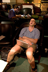 07 Sept 2005. New Orleans, Louisiana. Hurricane Katrina aftermath.<br /> <br /> Daily Mirror's Ryan Parry collapses in a chair as he struggles to catch up with limited sleep during his coverage of hurricane Katrina.<br /> Photo; ©Charlie Varley/varleypix.com