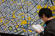 Tourist finding their way around Soho and the West End with the help of a large city map of London.