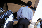 posterior view of business man on escalator
