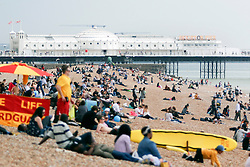 © Licensed to London News Pictures. 23/05/2015. Brighton, UK. People relax on the beach and enjoy the few moments of sunshine at the start of the May Bank Holiday Weekend, today May 23rd 2015. Photo credit : Hugo Michiels/LNP