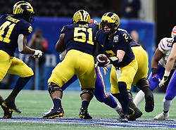 Michigan Wolverines quarterback Shea Patterson (2)  prepares to hand the ball off too Michigan Wolverines running back Christian Turner (41) during the Chick-fil-A Bowl Game at  the Mercedes-Benz Stadium, Saturday, December 29, 2018, in Atlanta. ( Kyle Hess via Abell Images for Chick-fil-A Kickoff)